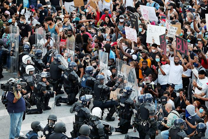 Police and protesters kneel together on June 1, 2020, in Minneapolis. Curtis Compton/Atlanta Journal-Constitution via AP