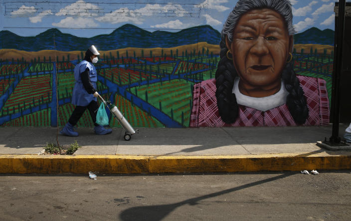 City worker Alexis Hernandez delivers a tank of oxygen to a COVID-19 patient, in the Iztapalapa borough of Mexico City, Friday, Jan. 15, 2021. The city offers free oxygen refills for COVID-19 patients. (AP Photo/Marco Ugarte)