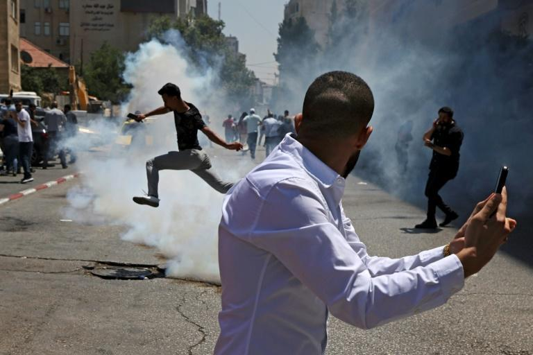 Protesters run for cover from tear gas fired by Palestinian security forces during a demonstration calling for Palestinian president Mahmud Abbas to quit