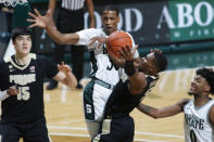 Purdue's Brandon Newman, right, goes to the basket but is blocked by Michigan State's Marcus Bingham Jr. as Purdue's Zach Edey, left, and Michigan State's Aaron Henry watch during the first half of an NCAA college basketball game Friday, Jan. 8, 2021, in East Lansing, Mich. (AP Photo/Al Goldis)