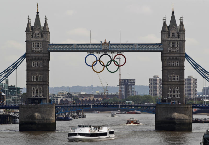 The Olympic rings are seen atop the iconic Tower Bridge over river Thames in London, after they were lowered into position, coinciding with one month to go until the start of London 2012 Games, Wednesday, June 27, 2012. The giant rings, which are fully retractable to allow for tall ships to pass through the bridge, will remain in position for the duration of the Games. (AP Photo/Lefteris Pitarakis)