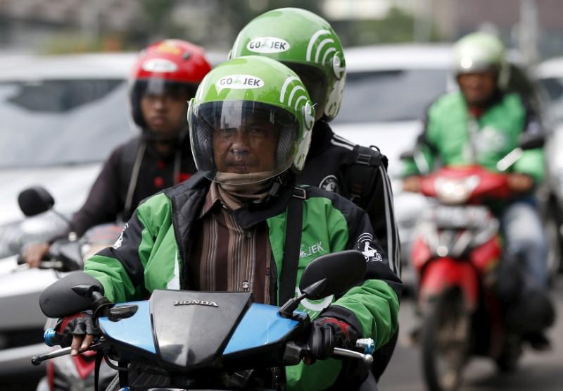 FILE PHOTO - Driver and passenger ride on a motorbike, part of the Go-Jek ride-hailing service, on a busy street in central Jakarta