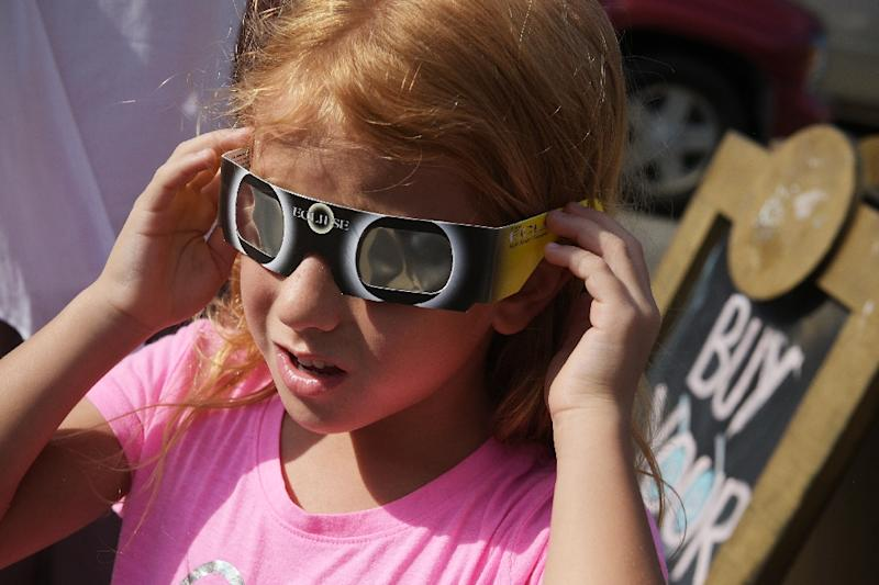 Zoe Spyridonos tries out eclipse glasses in Charleston, South Carolina ahead of the total solar eclipse on August 21, 2017 (AFP Photo/MANDEL NGAN)