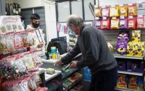 A man buys eggs from the Woburn Village Stores, a convenience store in Woburn, Britain