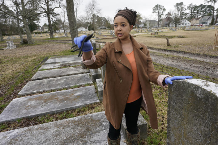Nadia Orton, a genealogist and family historian in Virginia, points out dilapidated areas next to tombstones at the Lincoln Memorial Cemetery in Portsmouth, Va., Tuesday, March 23, 2021. Orton has worked tracing her own family and others to historically Black cemeteries. (AP Photo/Steve Helber)