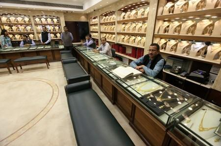 FILE PHOTO: Salespeople wait for customers at a gold jewelry showroom in Chandigarh