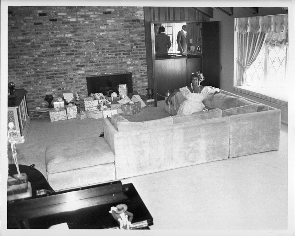 <p>The Queen of Soul lounges on the couch of her Detroit home, while keeping her eye on the hoard of Christmas presents displayed in front of her fireplace.</p>