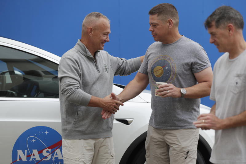 NASA astronauts Douglas Hurley, left, and Robert Behnken shake hands outside the Neil A. Armstrong Operations and Checkout Building, at the Kennedy Space Center in Cape Canaveral, Fla., Wednesday, May 27, 2020. The two astronauts will fly on a SpaceX test flight to the International Space Station. For the first time in nearly a decade, astronauts will blast into orbit aboard an American rocket from American soil, a first for a private company. (AP Photo/John Raoux)