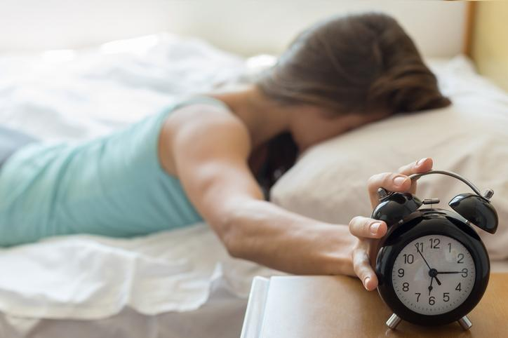 A girl is pictured touching her alarm clock.