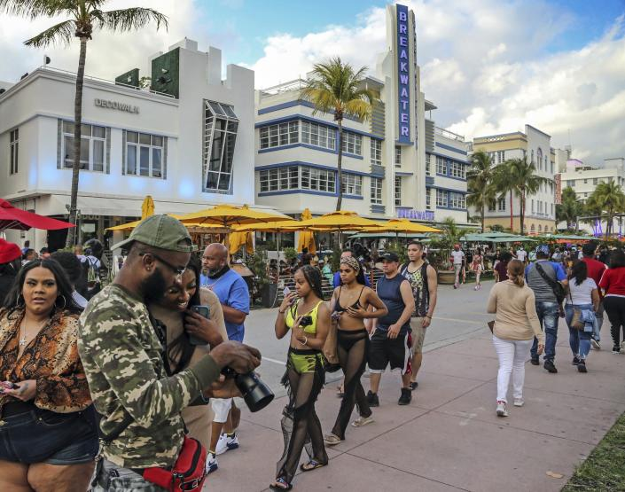 Despite the coronavirus, spring breakers return to South Beach and walk along Ocean Drive that is closed to traffic on Thursday, March 12, 2021. Miami Beach officials are imposing an emergency 8 p.m.-6 a.m. curfew effective immediately, saying large, out-of-control spring break crowds crammed the beaches, trashed some restaurant properties and brawled in the streets. Tourists and hotel guests are being told to stay indoors during the curfew hours. (Al Diaz/Miami Herald via AP)