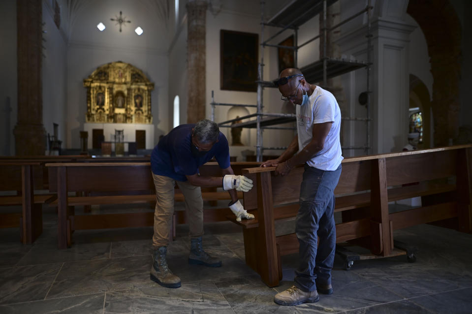 Workers set up a bench inside the San Jose Church, the second oldest Spanish church in the Americas, that will reopen following massive reconstruction that has taken nearly two decades to complete, in San Juan, Puerto Rico, Tuesday, March 9, 2021. The church was built for a Dominican convent where the renowned Spanish priest Bartolomé de las Casas once lived. (AP Photo/Carlos Giusti)
