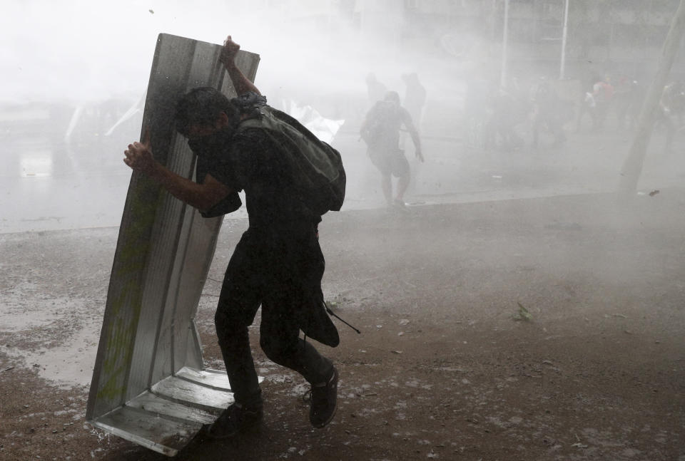 An anti-government protester uses a piece of sheet metal to protect himself from the jet spray of a police water cannon in Santiago, Chile, Friday, Nov. 8, 2019. Chile's president on Thursday announced measures to increase security and toughen sanctions for vandalism following three weeks of protests that have left at least 20 dead. (AP Photo/Esteban Felix)