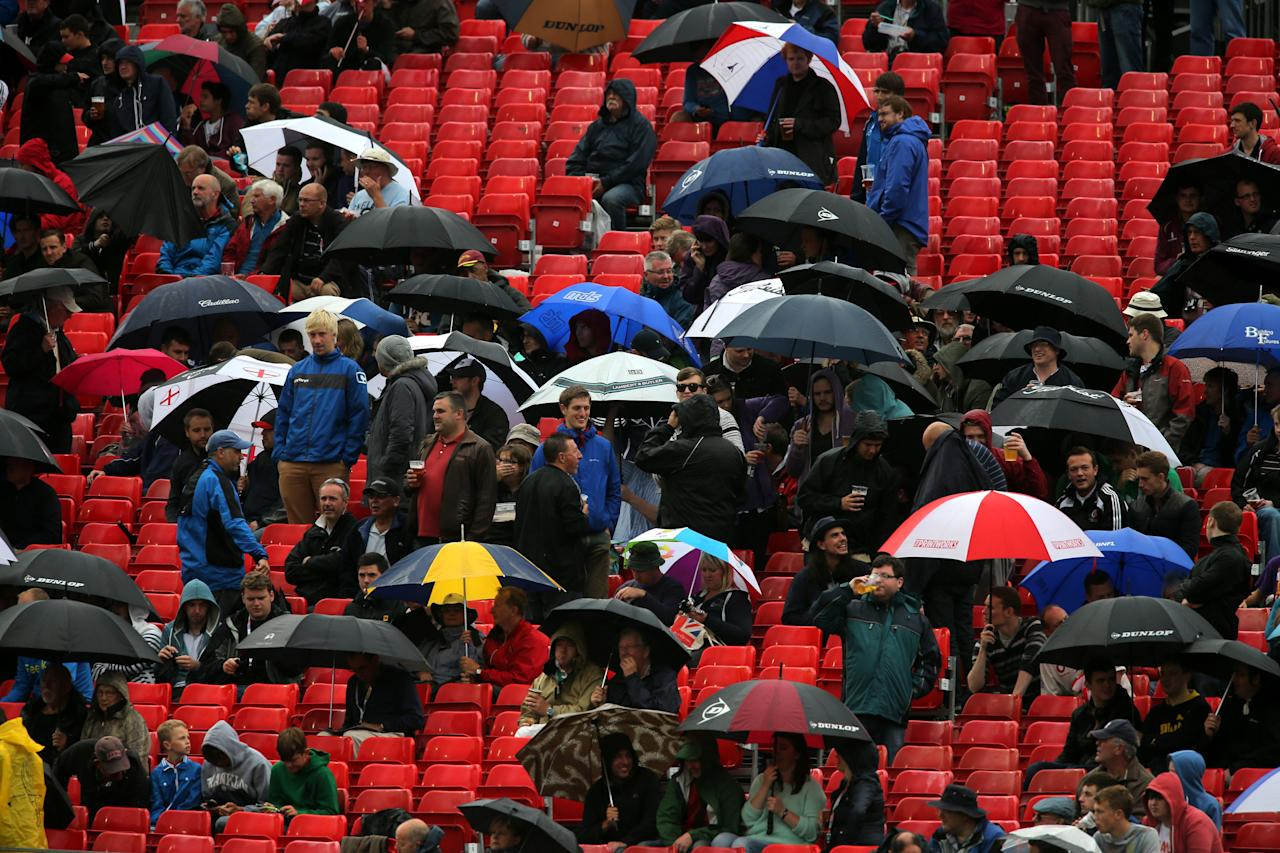 Cricket fans watch the rain fall as rain stops play just after lunch , during day five of the Third Investec Ashes test match at Old Trafford Cricket Ground, Manchester.