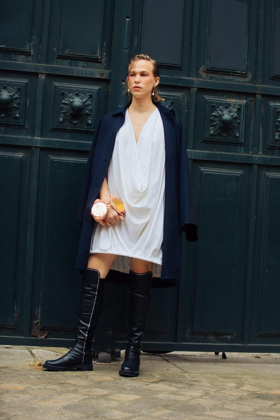 <p>She styled a billowing white dress with a pink bag, Stuart Weitzman knee-high boots, and a long coat.</p>