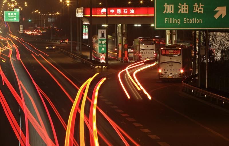 Cars drive into a Petrol China gas station, as other vehicles drive past on the Beijing-Tibet expressway in Beijing