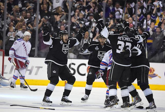 Los Angeles Kings' Dustin Brown, second from left, celebrates his game-winning goal with teammates as New York Rangers defenseman Ryan McDonagh skates at left in the second overtime period in Game 2 of the NHL hockey Stanley Cup Finals, Saturday, June 7, 2014, in Los Angeles. The Kings won 5-4. (AP Photo/Mark J. Terrill)