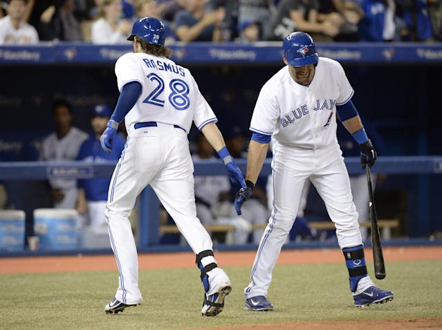 Toronto Blue Jays' Colby Rasmus, left, celebrates his solo home run with teammate Mark DeRosa against the New York Yankees during fourth inning MLB American League baseball action in Toronto, Tuesday, Sept.17, 2013. (AP Photo/The Canadian Press, Frank Gunn)