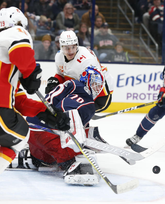Columbus Blue Jackets' Joonas Korpisalo, front, of Finland, makes a save against Calgary Flames' Mikael Backlund, of Sweden, during the third period of an NHL hockey game Saturday, Nov. 2, 2019, in Columbus, Ohio. (AP Photo/Jay LaPrete)