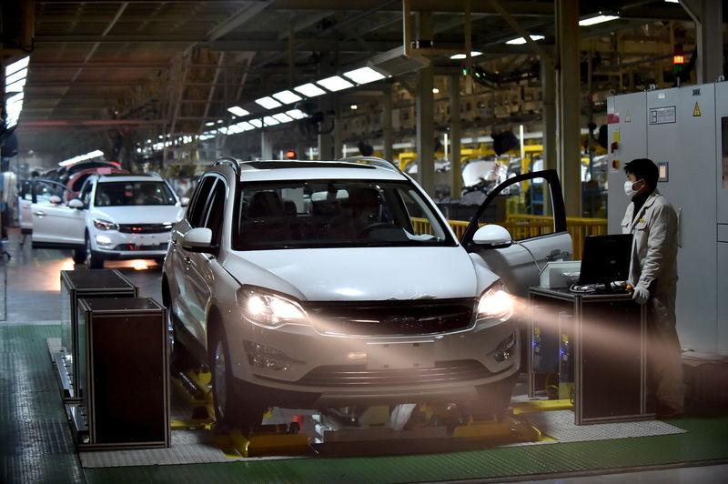 Employees work at a production line at inside an automobile factory in Hangzhou