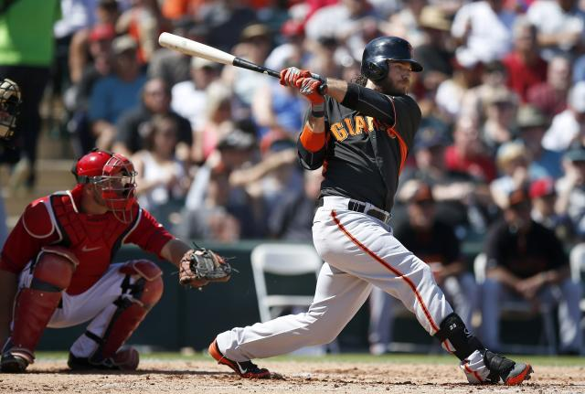 San Francisco Giants' Brandon Crawford, right, connects for a double as Los Angeles Angels' Chris Iannetta looks on during the third inning of a spring training baseball game Monday, March 24, 2014, in Tempe, Ariz. (AP Photo/Ross D. Franklin)
