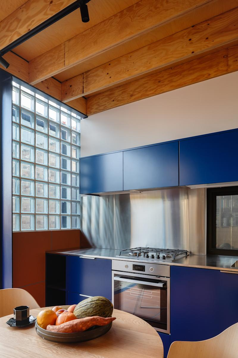 The kitchen features cabinetry in a royal blue hue, which is carried throughout the addition.