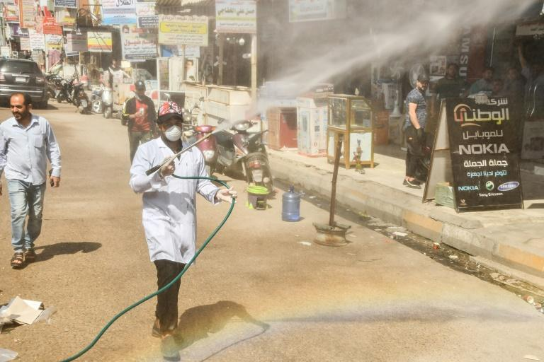 A municipality worker disinfects a street in Iraq's southern city of Nasiriyah as a precaution against the coronavirus outbreak