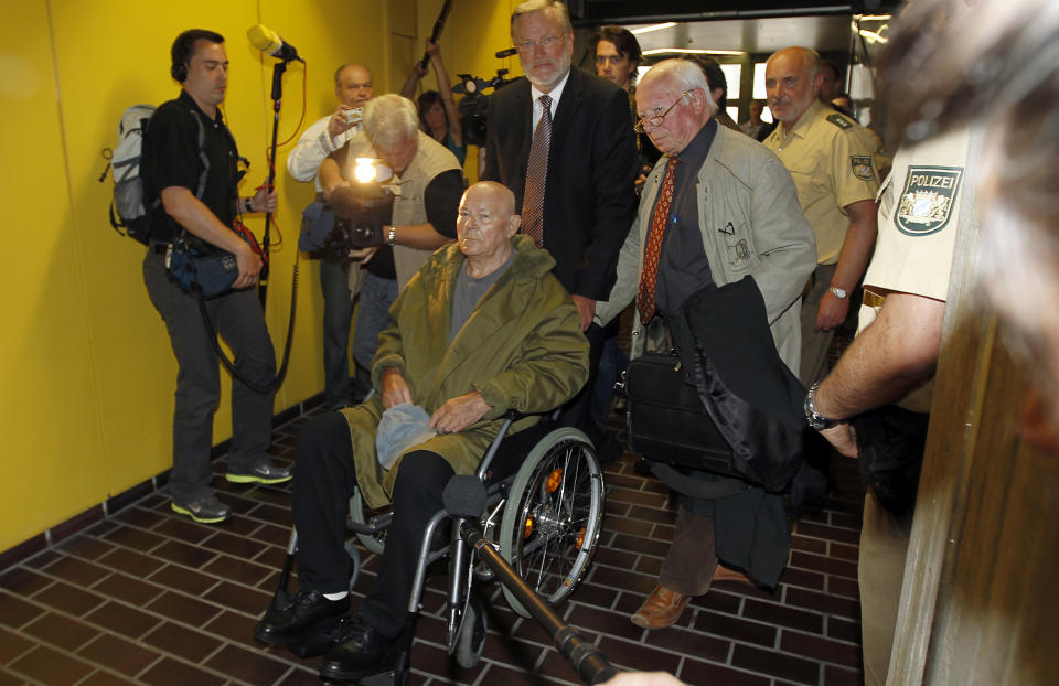 John Demjanjuk leaves the court room with his lawyers Ulrich Busch, center, and Guenther Maull, right, in Munich, southern Germany, on Thursday, May 12, 2011. The court has ordered John Demjanjuk released pending an appeal of his conviction as an accessory to murder at a Nazi death camp. (AP Photo/Matthias Schrader)