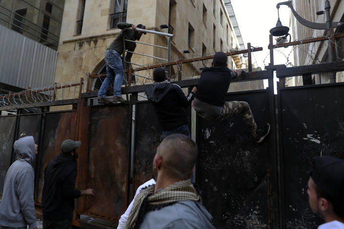 Anti-government protesters climb a metal wall installed by security forces to prevent protesters from reaching the Parliament building, during a protest in Beirut, Lebanon, Saturday, March. 13, 2021. Riot police fired tear gas to disperse scores of people who protested near parliament building in central Beirut Saturday amid deteriorating economic and financial conditions and as the local currency hit new low levels. (AP Photo/Bilal Hussein)
