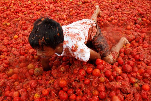 "A reveller plays with tomato pulp during the annual ""Tomatina"" (tomato fight) in Sutamarchan Province in Boyaca June 10, 2012. REUTERS/John Vizcaino"