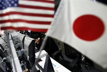 An employee of a foreign exchange trading company working is seen between the national flags of Japan and the U.S. in Tokyo