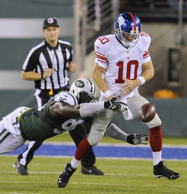 New York Jets linebacker Antwan Barnes (95) strips the ball from New York Giants quarterback Eli Manning (10) in the second quarter of a preseason NFL football game, Friday, Aug. 22, 2014, in East Rutherford, N.J. The ball bounced out of bounds on the play. (AP Photo/Bill Kostroun)