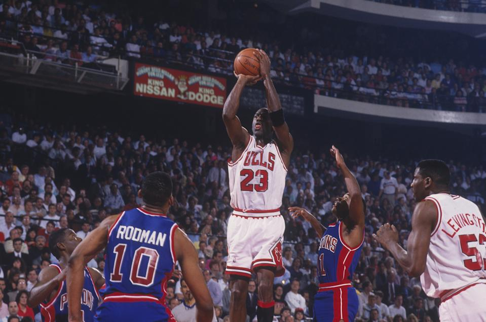 CHICAGO - 1991: Michael Jordan #23 of the Chicago Bulls jumps to shoot a basket against the Detroit Pistons as Cliff Levingston #53 of the Bulls, Dennis Rodman #10 of the Pistons and Isiah Thomas #11 of the Pistons watch the shot at the Chicago Stadium during the 1991 NBA Playoffs in Chicago, Illinois. (Photo by Focus on Sport via Getty Images)