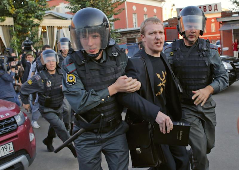 Police officers detain an ultra Orthodox activist outside the Vinzavod art gallery in Moscow, Russia, Thursday, Sept. 20, 2012. A protest by about 15 Russian Orthodox Christian activists has disrupted the opening of a Moscow art exhibit inspired by the jailed members of the punk band Pussy Riot. Riot police dispersed the protesters, detaining nine of them, but then blocked off the area, making it difficult for those who wanted to attend Thursday's opening to get inside. The paintings by Yevgenia Maltseva were inspired by religious icons and the three Pussy Riot members who were jailed for a raucous performance inside a Moscow cathedral to protest Vladimir Putin's rule and his close relationship with the church hierarchy. (AP Photo/Alexander Zemlianichenko)