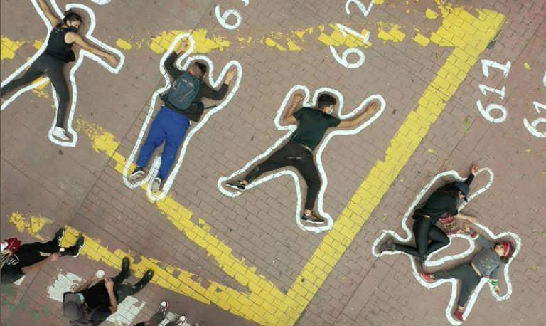 """People lie on painted silhouettes simulating dead bodies, protesting for thousands of extrajudicial executions known as """"false positives"""" and perpetrated by Colombian military forces, in Bogota on June 4, 2021"""