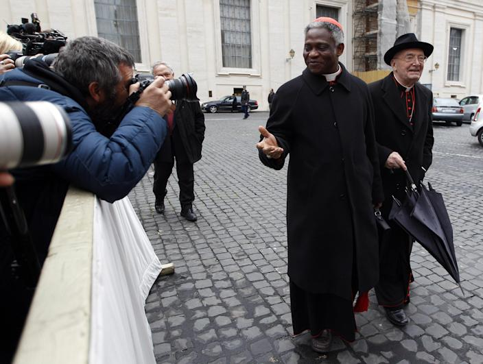 """Cardinal Peter Kodwo Appiah Turkson, center, is photographed by the media as he arrives for an afternoon meeting, at the Vatican, Friday, March 8, 2013. The Vatican says the conclave to elect a new pope will likely start in the first few days of next week. The Rev. Federico Lombardi told reporters that cardinals will vote Friday afternoon on the start date of the conclave but said it was """"likely"""" they would choose Monday, Tuesday or Wednesday. The cardinals have been attending pre-conclave meetings to discuss the problems of the church and decide who among them is best suited to fix them as pope. (AP Photo/Alessandra Tarantino)"""