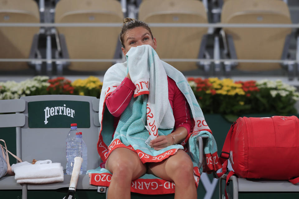 Romania's Simona Halep sits on the bench during a switch of sides in the fourth round match of the French Open tennis tournament against Poland's Iga Swiatek at the Roland Garros stadium in Paris, France, Sunday, Oct. 4, 2020. (AP Photo/Michel Euler)