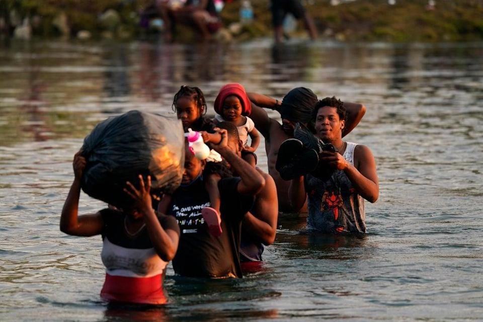 Migrants, many from Haiti, wade across the Rio Grande from Del Rio, Texas, to return to Ciudad Acuna, Mexico, Tuesday, 21 September 2021, to avoid deportation from the U.S (AP)