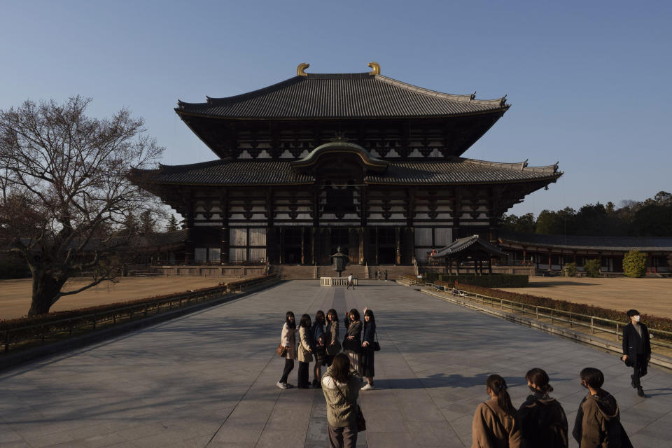 Tourists pause for photos in front of Todaiji temple's main hall in Nara, Japan, March 17, 2020. Nara was among the first Japanese town hit by the COVID-19 in late January, when a tour bus driver in town tested positive for the virus, becoming the first Japanese patient after carrying tourists from Wuhan, the epicenter of the pandemic. (AP Photo/Jae C. Hong)