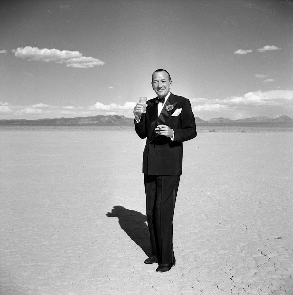 <p>In a photo that sells the allure of the desert, actor Sir Noël Coward poses in a tuxedo with a cocktail and a cigarette in 1955. </p>