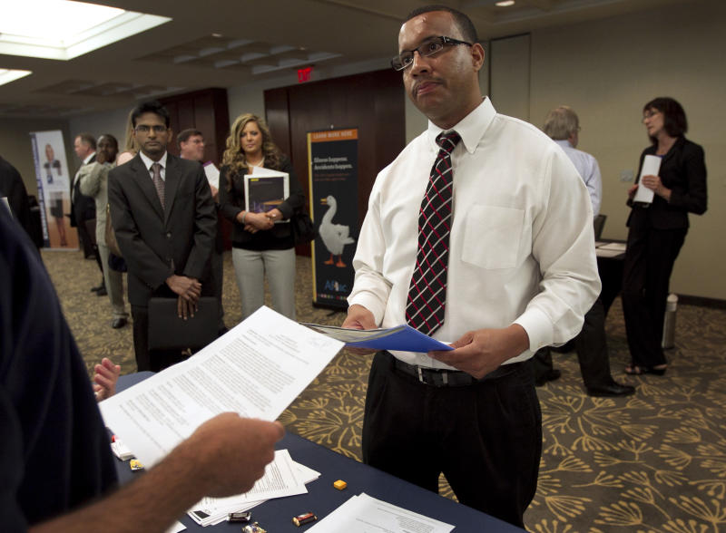 In this Monday, June 18, 2012 photo Trey Fortes, right, speaks with Jason Monteiro, of Hudson, Mass., left, during a job fair in Boston. The number of people seeking U.S. unemployment benefits dipped last week but not by enough to indicate hiring will pick up. Weekly applications for unemployment aid declined by 2,000 to a seasonally adjusted 387,000, the Labor Department said. That's down from an upwardly revised 389,000. (AP Photo/Steven Senne)