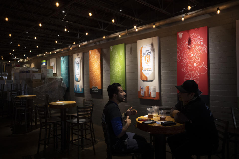 FILE - In this June 29, 2020, file photo, two men drink beers at the Mike Hess brewery and tasting room in San Diego. Authorities are closing honky tonks, bars and other drinking establishments in some parts of the U.S. to stem the surge of COVID-19 infections — a move backed by sound science about risk factors that go beyond wearing or not wearing masks. (AP Photo/Gregory Bull, File)