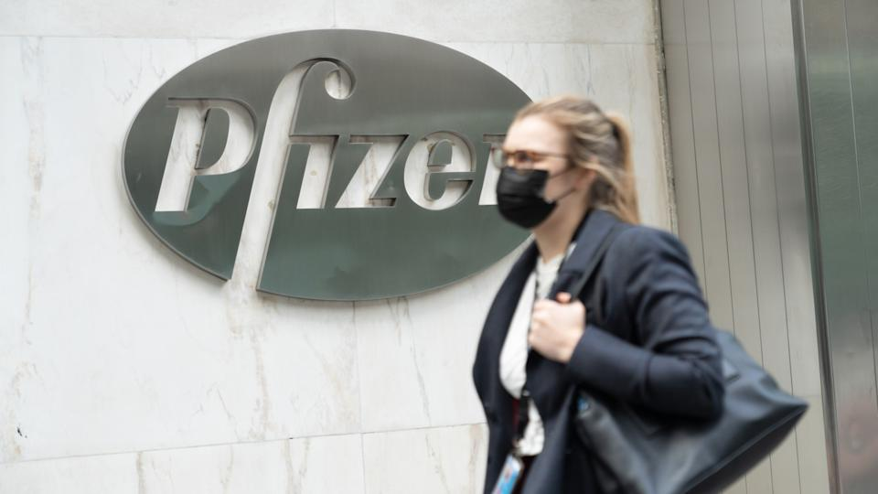 A woman wearing a face mask walks past a Pfizer logo at their Headquarters. (John Nacion/SOPA Images/LightRocket via Getty Images)