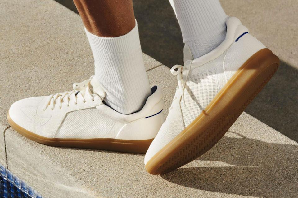 Man wearing white lace up low top sneakers