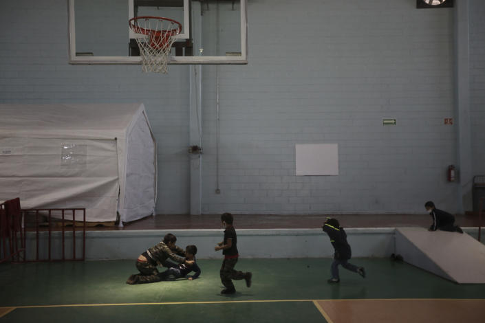 Children play in the Kiki Romero Sports Complex migrant shelter after they were deported from the U.S., in Ciudad Juarez, Mexico, Wednesday, April 21, 2021. Mexico said it is planning to set up 17 shelters for underage migrants along the country's southern border, as well as some along the northern border with the United States, amid a wave of child migrants coming from Central America. (AP Photo/Christian Chavez)