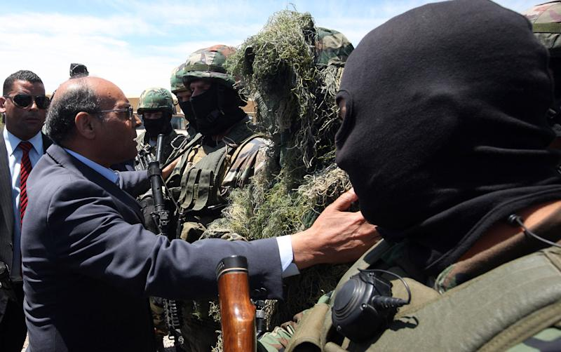 This photo provided by the Tunisian Presidency shows Tunisian President Moncef Marzouki, second left, visiting members of National Guard, hooded, and military officials in Jebel Chaambi, western Tunisia and close to the Algerian border, Tuesday, May 7, 2013. Tunisia's Defence Ministry says the army has surrounded a group of armed militants holed up in a mountain stronghold protected by homemade fertilizer bombs. (AP Photo/Tunisian Presidency)