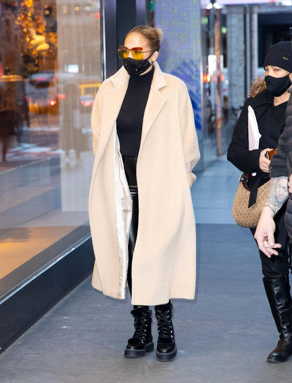 """<p>The 51-year-old was photographed enjoying a spot of Christmas shopping on December 8.</p><p>For the outing, the singer wore a pair of black combat boots, skin-tight leggings, a camel-coloured long coat and orange-tinted sunglasses. She also wore a black face mask.</p><p><a class=""""link rapid-noclick-resp"""" href=""""https://www.elle.com/uk/fashion/what-to-wear/articles/g31087/best-camel-coats-to-buy-now-high-street-topshop-mango-warehouse/"""" rel=""""nofollow noopener"""" target=""""_blank"""" data-ylk=""""slk:SHOP CAMEL COATS"""">SHOP CAMEL COATS</a></p>"""