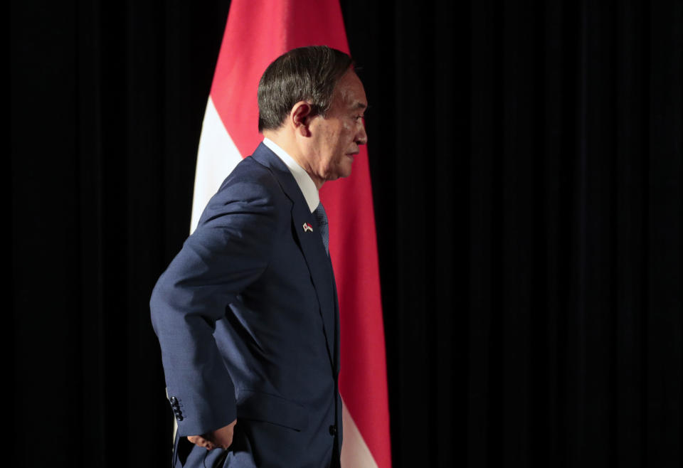 Japanese Prime Minister Yoshihide Suga walks past Indonesian national Red-White flag as he arrives for a press conference in Jakarta, Indonesia, Wednesday, Oct. 21, 2020. Suga is on a four-day visit to Vietnam and Indonesia. (AP Photo/Dita Alangkara, Pool)