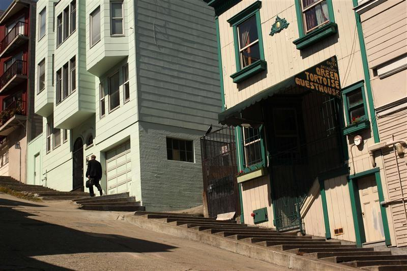 A man climbs a set of stairs built into the sidewalk in the North Beach neighborhood in San Francisco, California.