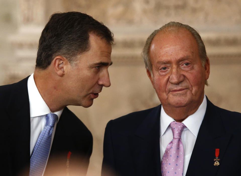 FILE - In this Wednesday June 18, 2014 file photo, Spanish Crown Prince Felipe, left speaks with Spanish King Juan Carlos after he signed an abdication law during a ceremony at the Royal Palace in Madrid, Spain. Former Spanish King Juan Carlos I has paid close to 4.4 million euros ($5.33 million) in a debt with the country's tax authorities it was announced Friday, Feb. 26, 2021, his latest attempt to regularize past undeclared income. The former monarch has been living abroad for more than half a year after media revealed fresh allegations of financial misdoings. (AP Photo/Daniel Ochoa de Olza)