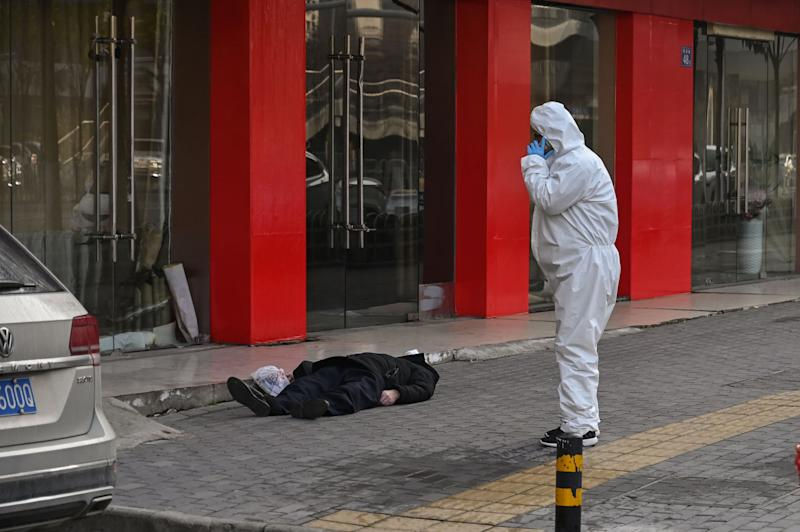 EDITORS NOTE: Graphic content / This photo taken on January 30, 2020 shows an official in a protective suit checking on an elderly man wearing a facemask who collapsed and died on a street near a hospital in Wuhan. - AFP journalists saw the body on January 30, not long before an emergency vehicle arrived carrying police and medical staff in full-body protective suits. The World Health Organization declared a global emergency over the new coronavirus, as China reported on January 31 the death toll had climbed to 213 with nearly 10,000 infections. (Photo by Hector RETAMAL / AFP) / TO GO WITH China-health-virus-death,SCENE by Leo RAMIREZ and Sebastien RICCI (Photo by HECTOR RETAMAL/AFP via Getty Images)